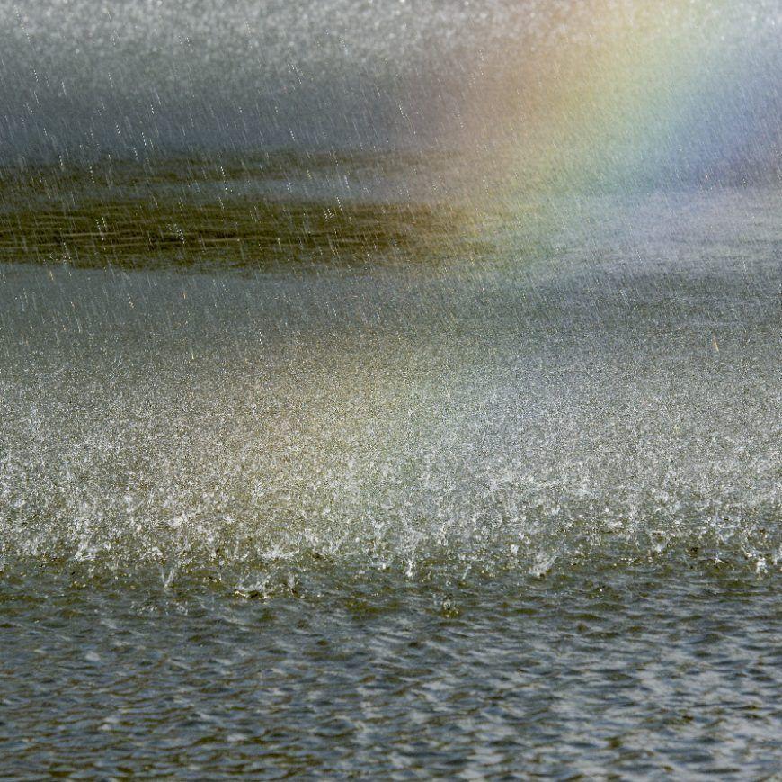 Gotas salpicando la superficie del agua bajo los tonos del arcoiris