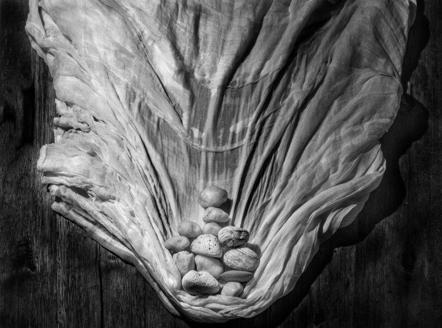 Fotografía artística bodegón de tela mojada arrastrada por cantos rodados sobre una tabla de madera