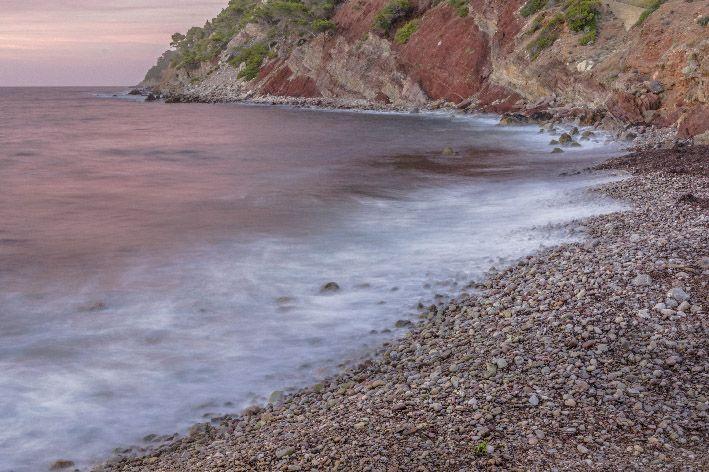 Reflejos púrpuras sobre el mar tras puesta de sol