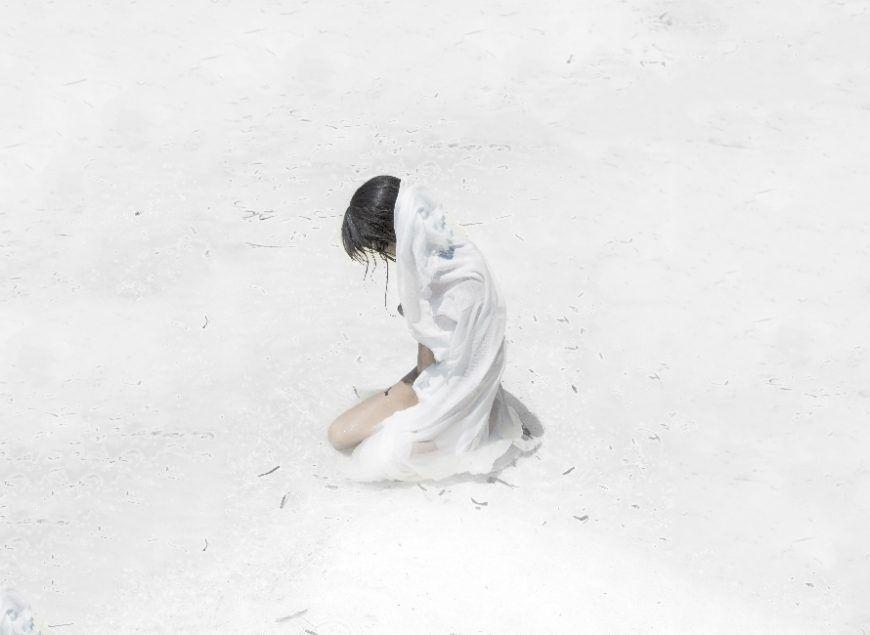 mujer arrodillada en arena blanca cubierta con tela blanca