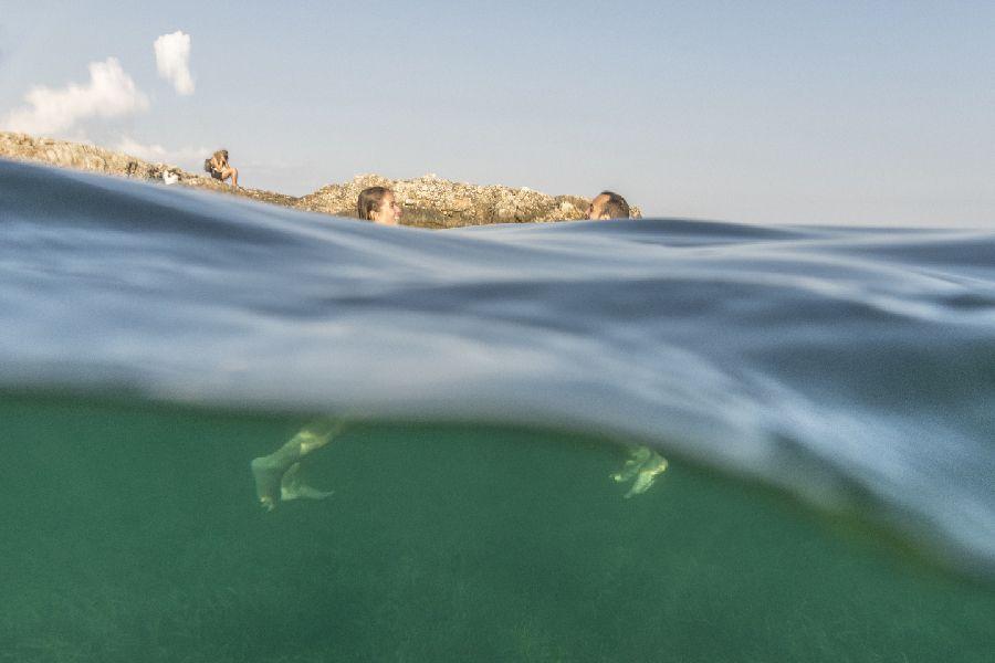 foto entre el mar y el cielo con dos bañistas