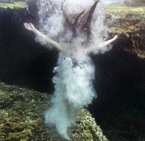 Primer plano de Joven mujer bajo el agua del mar con los brazos en cruz con muchas burbujas de aire