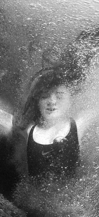 Primer plano de Joven mujer bajo el agua del mar con los brazos en cruz