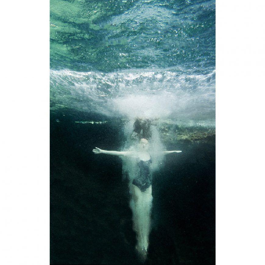 Joven mujer bajo la superficie del mar con los brazos en cruz